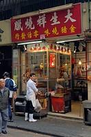 Hong Kong, China, Asia. Hong Kong Kowloon. Roadside butcher using a telephone while working.
