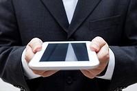 Detail of businessman holding digital tablet.