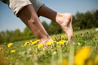 Bare feet walking on meadow