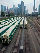 Several Go Trains resting with the Toronto skyline in the background. Toronto, Ontario, Canada.