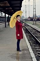 Mid adult woman standing on railroad station platform holding umbrella.
