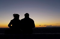 Couple watching sunset, Es Codolar Boulder beach, Eivissa, Ibiza, Balearic Islands, Spain, Mediterranean, Europe.