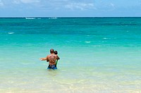 USA, Hawaii, Oahu. Kailua Beach on the west coast. A father holding his young child on the edge of the ocean.