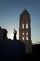 Silhouette of a woman taking photo near the Panagia Kimissis church situated at the cliff in Hora, Folegandros, Cyclades Islands, Greek Islands, Greec...