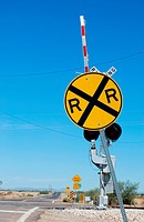 Railroad crossing sign with the gates up.