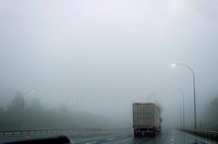 A truck drives in heavy, dripping fog on a highway, Nova Scotia.