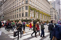 Shoppers cross Fifth Avenue across from Saks Fifth Avenue the last weekend before the Christmas holiday.