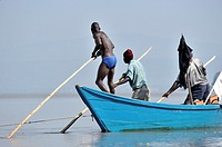 Fishers pushing their boat through the water at Lake Victoria, Kenya.