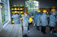 Children putting on hard hats and coats preparing to descend into the pit mine dating from 1156, Mining Museum, UNESCO site, Banska Stiavnica, Slovaki...