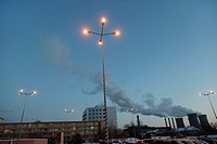 Street lamps on in a parking lot at dusk, with Grozavesti Power Station in the background - Bucharest, Romania, Europe, Eastern Europe.