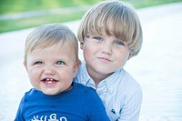 Portrait a baby and his older brother smiling at camera