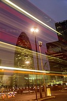 London, UK, The City - Almost invisible Double-decker bus zipping in front of the Gherkin Building at night
