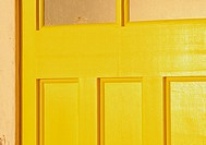 Sunlight on bright yellow painted wooden door, St Ives, Cornwall, England, Europe.