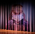 A stage curtain with the face of a scary doctor appearing on it.