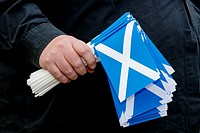 Man holding a number of small plastic saltire flags, Scotland.