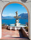 Window view with a water fountain with statue and panoramic view over alpine lake Maggiore with snow-capped mountains in a sunny day with blue sky in ...