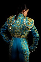 Woman bullfighter suit with blue lights on a black background.