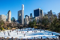 New York, USA. View on the Ice Rink in Central Park, Manhattan, with 5th Avenue & 59th Street skyscrapers in the background.