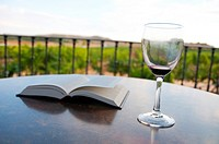 Empty glass of red wine and open book.