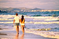 Couple on the beach walking back. Costa Daurada, Costa Dorada, Catalonia, Spain.