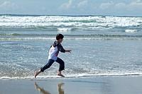 A boy has fun running on the beach in the water in Newport, Oregon.