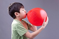 A young boy blows up a red baloon.