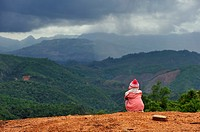 sitting child admiring landscape at a mountain pass on the road 13, around Udomxay, Oudomxay Province in northwestern Laos, Southeast Asia.