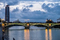 Isabel II bridge and Modern tower skycrapper built in Seville. Tower designed by Cesar Pelli, from Triana district by sunset. Seville, Andalusia, Spai...