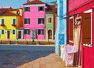 Small square of brightly painted houses looking out on canal, Burano, Venetian Lagoon, Veneto, Italy, Europe.