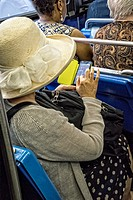 Undentifiable Woman in a White Hat, sitting on the Madison Avneue uptown bus, delicaely working her smart phone.