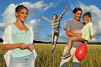 young parents playing with their children in a field, Ile-de-France, France, Europe.