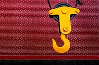 Industrial Hook - Bright yellow crane hook against a red brick wall.