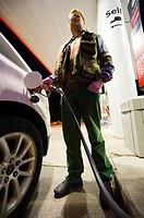 young man filling in the car tank at a gas station.
