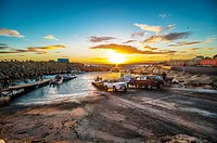 Small fishing boats ski boats are launched on a broad slipway as the sun rises over the sea. Cape Town, South Africa