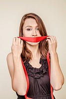 Young woman holding a red ribbon over her mouth.