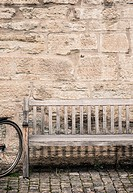 Empty wooden bench and bicycle in front of weathered stone wall.
