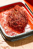 Saffron in a red laquer box. Close up of spice. Concept of culinary cooking.