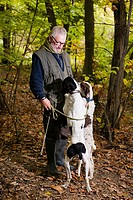 Elderly man caresses his dogs while looking for truffles in the woods one of the dogs looks into his pocket.