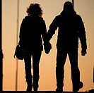 A rear view of two people couple walking hand in hand in silhouette at dusk UK.