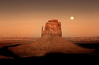 A full moon rises above a snow-covered Monument Valley, Arizona.