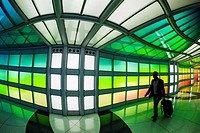 Travelers in tunnel at United terminal passing Sky´s the Limit (neon sculpture by artist Michael Hayden) at O´Hare International Airport, Chicago, Ill...