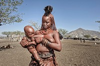 Himba woman breast feeding her child in her village.