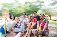 mixed ethnic friends spinning on merry go round in playground laughing with black, vietnamese, hispanic, white people in their 20´s and 30´s MR-9, MR-...