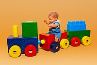 Wooden toy train with a doll boy riding on it.
