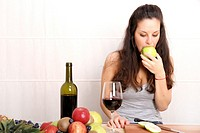 A young adult woman with fruits and wine in the kitchen.