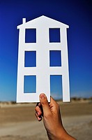 Hand holding house shape on an empty plot of land - design, construction, new homes concept.