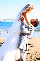 happy groom lifting his bride on beach after wedding
