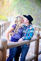 engaged couple in a park kissing