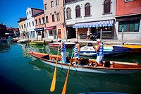 Group of mature men riding a gondola in a canal of Murano, Venice, Italy.