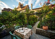 France, Midi-Pyrénées, Carrenac. Table and chairs set up in small private garden in the medieval village. Officially classified as one of the most bea...